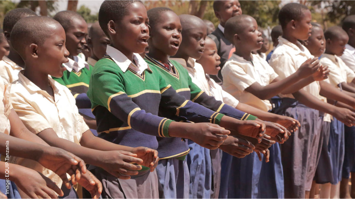 Tanzanian children in school uniform lined up and singing