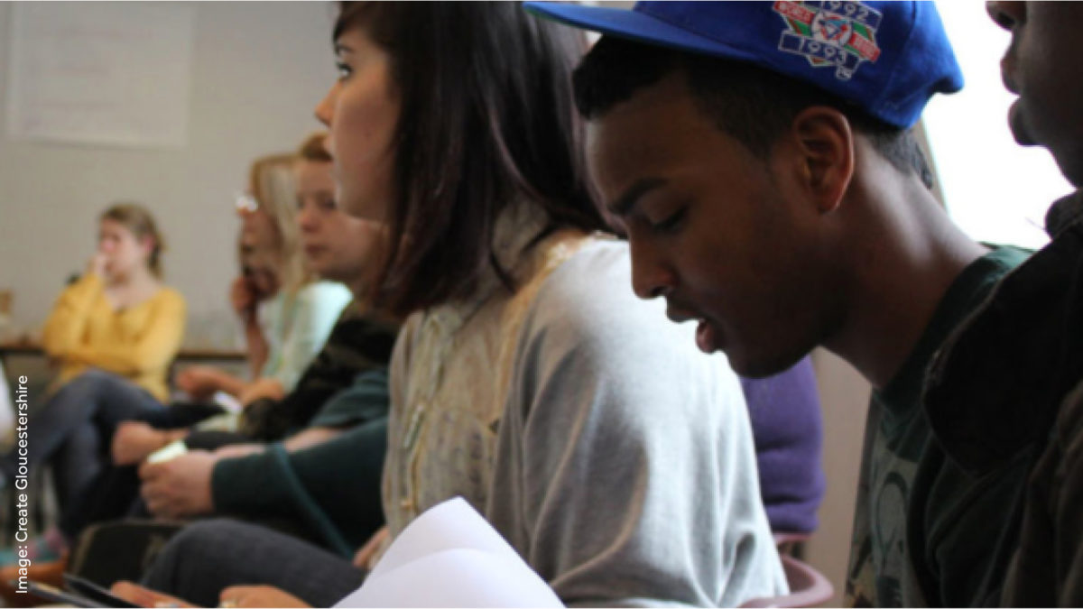 Two young people in a workshop, one wearing a cap looking down at some paper