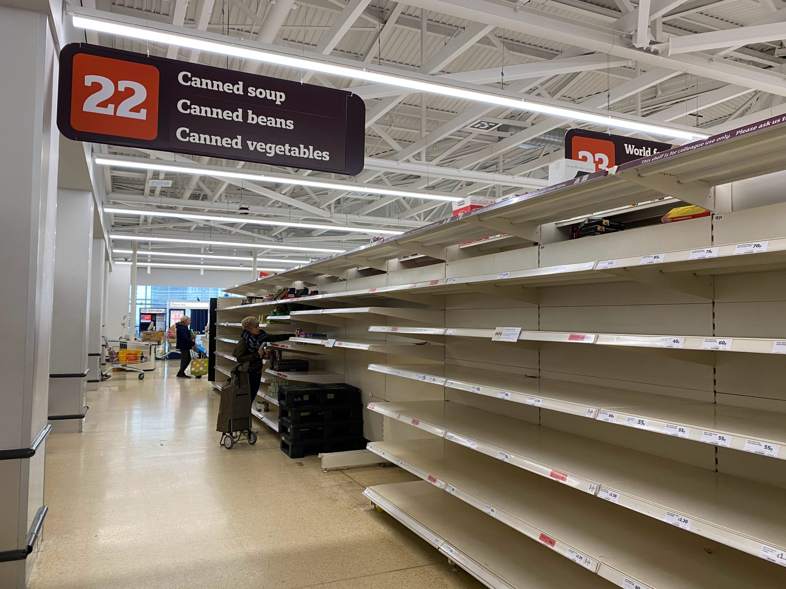 Aisle in supermarket with near empty shelves